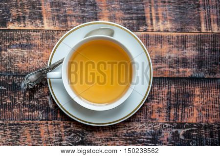 Herbal tea in white china cup on colorful wooden background