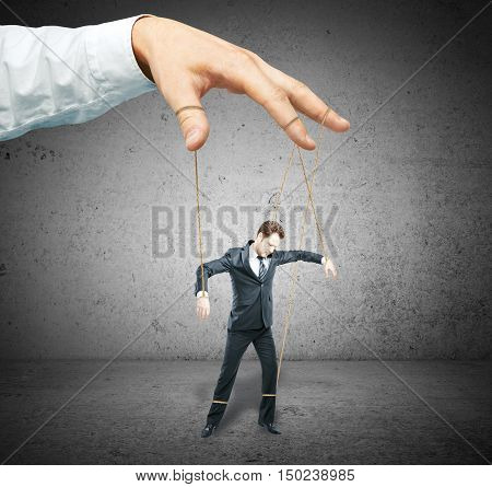 Hand controlling businessman as puppet on concrete background. Control concept