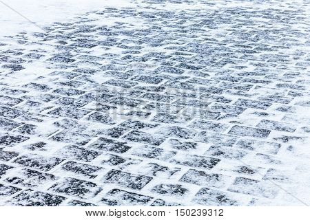 Sidewalk Cobblestone pavement covered with snow and ice