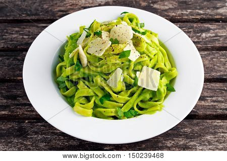 Tagliatelle pasta with spinach, avocado and parmigiano cheese, herbs in white plate. concept of healthy food.