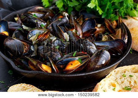 Boiled mussels in iron pan cooking dish. with herbs, butter, lime, parsley, garlic and fresh bread