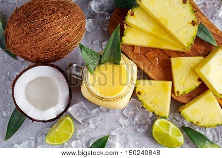 Healthy ripe Yellow Pineapple, coconut, Smoothie with slices of Lime and ice. concept healthy food.