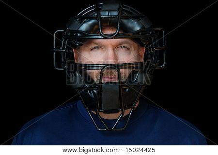 Baseball Umpire.  Head shot of handsome middle-aged man wearing an umpire's mask.  Isolated against black background.