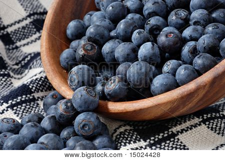 Freshly washed blueberries spilling out of a wooden bowl onto a handwoven dish towel.  Close-up with shallow dof.