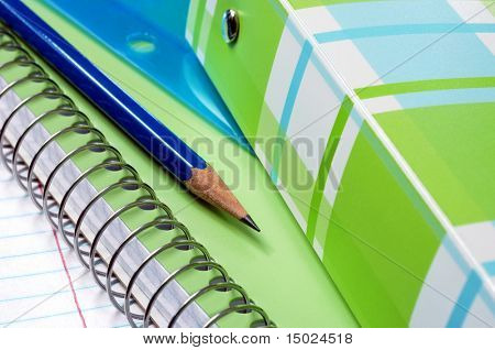 Colorful notebooks with paper and pencil.  Macro with selective focus on pencil point.