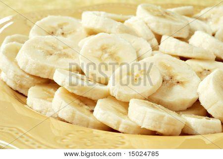 Freshly sliced bananas on a decorative plate.  Macro with shallow dof.
