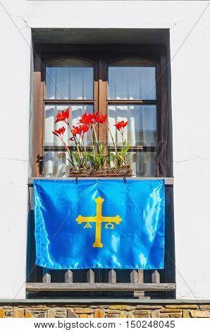 Asturias flag hanging on a balcony with a flowerpot. Taramundi Asturias Spain
