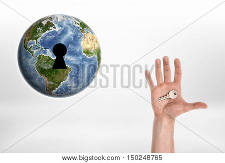 Human hand with the key from planet Earth. Enviroment protection. Protection of Nature. Resource usage. Elements of this image are furnished by NASA.