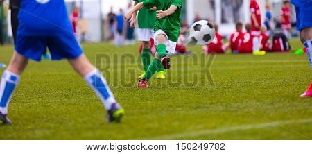 Football kick. Soccer ball in motion. Young soccer player kicking soccer game on sports field.