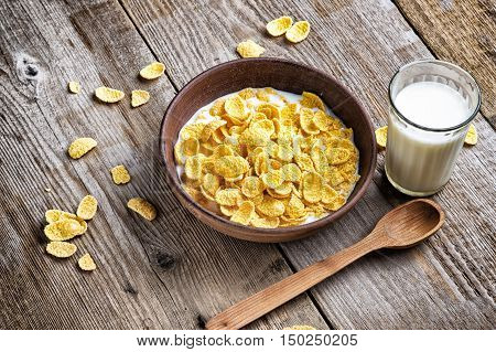 on a wooden surface - cereal with milk in a clay plate lies next to wooden spoon is a glass of milk. healthy cereal breakfast