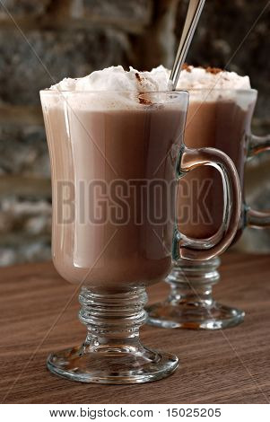 Hot chocolate or coffee latte in irish coffee mugs with stone wall in background.  Macro with extremely shallow dof.