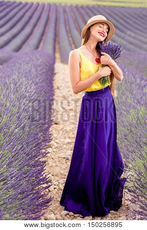 Young and pretty woman in the long violet skirt standing with lavender bouquet on the lavender field in Provence in France