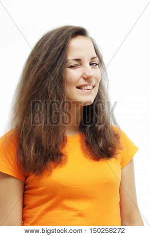 Close-up portrait of brunette girl winking and smiling. Over white background. Winking woman with long wavy hair. Attractive woman in an orange T-shirt.