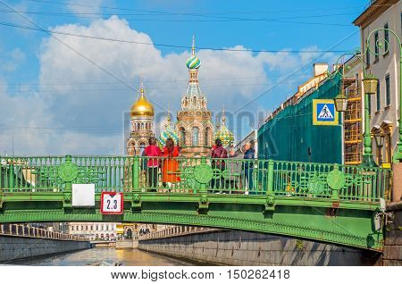 ST PETERSBURG RUSSIA-OCTOBER 3 2016. Cathedral of Our Saviour on Spilled Blood and Italian bridge over Griboedov channel with tourists watching the St Petersburg landmarks in St PetersburgRussia