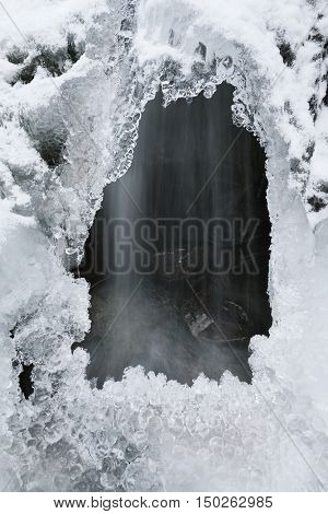 River under the ice and snow. Beautiful icicles