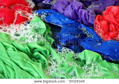 Brightly colored laundry with sudsy water in washing machine.  Close-up with shallow dof.
