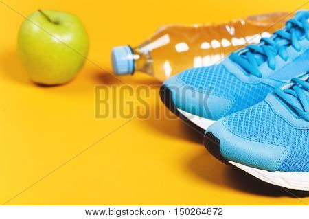 Blue sneakers, water and apple on black background. Concept of healthy lifestile and food, everyday training and force of will.