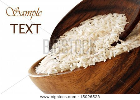 Uncooked rice in wooden bowl with spoon on white background with copy space.  Macro with shallow dof.