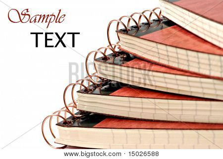 Stack of spiral bound notebooks on white background with copy space.  Macro with shallow dof.  Focus on spirals.