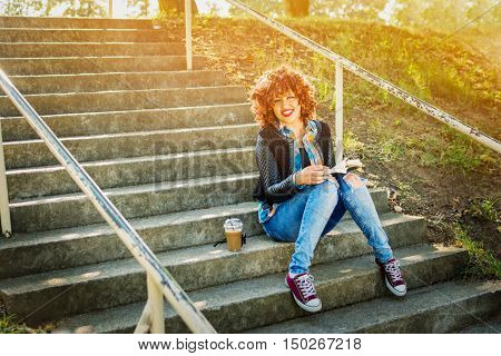 Cool teenage girl reading a book outdoors sitting on stairs. Modern millennial young redhead curly happy woman with book and takeaway coffee in park relaxing. Natural light, vibrant colors.