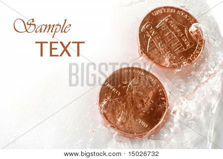 Shiny new pennies frozen in ice with copy space.  Financial concepts -  'frozen assets' , 'budget freeze', or 'cold hard cash'