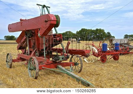 Old restored farm machinery including a wooden threshing machine, two corn planter and grain drill are lined up a farm show with a team of horses in the background