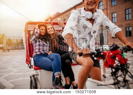 Shot of female friends taking selfie on tricycle. Young man riding tricycle bike with women sitting at back taking self portrait.