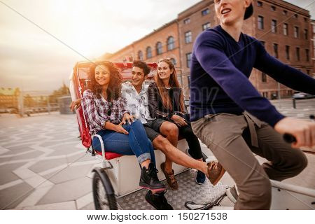 Group of teenagers traveling on tricycle in the city. Young men and women riding on tricycle on road.