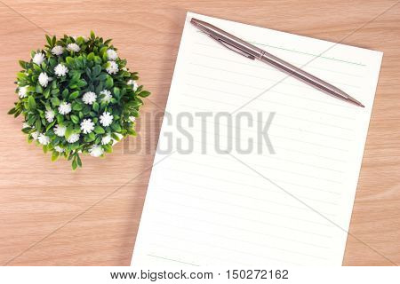 blank paper on desk / Open blank white paper notebook with copy space and a pen lying on a wood desk, view from above / for your text or message / top view