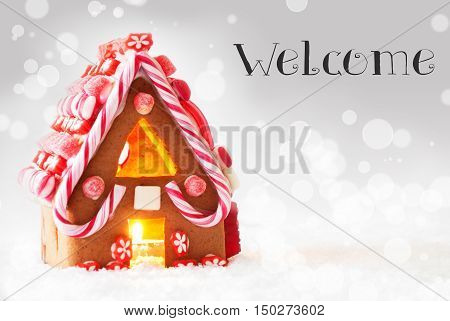Gingerbread House In Snowy Scenery As Christmas Decoration. Candlelight For Romantic Atmosphere. Silver Background With Bokeh Effect. English Text Welcome