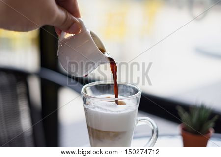 man hand pour hot fresh latte coffee cream in see through glass and white shinning latte coffee in pot with silver spoon on glass table at coffee time/ man hand pour hot fresh latte coffee
