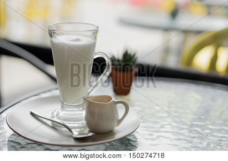 hot fresh latte coffee cream in see through glass and white shinning latte coffee in pot with silver spoon on glass table at coffee time not yet pour/ hot fresh latte coffee