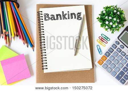 banking text message on white paper and office supplies, pen, paper note, on white desk , copy space / business concept / view from above, top view