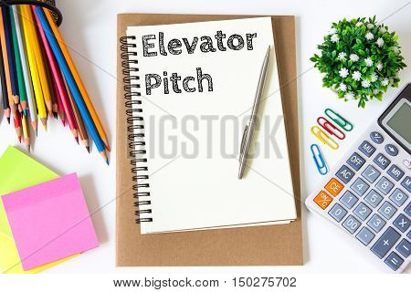 elevator pitch text message on white paper and office supplies, pen, paper note, on white desk , copy space / business concept / view from above, top view