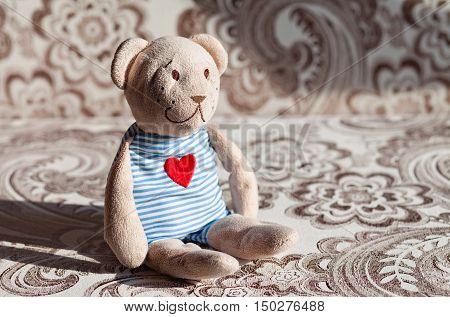 children's soft toy teddy bear sits on the couch in the nursery.