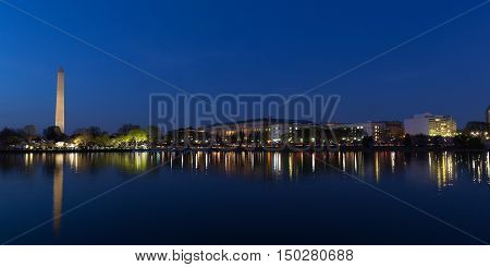 Night panorama of Washington DC during cherry blossom festival. Washington Monument and lights reflection in Tidal Basin waters.