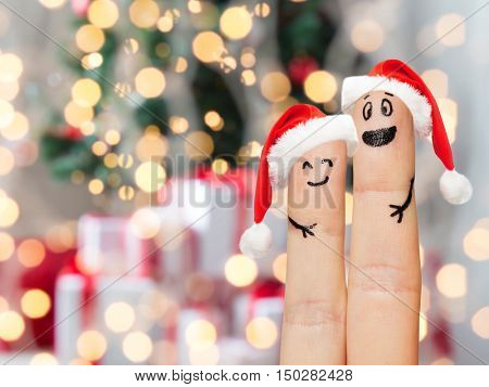 family, holidays, christmas and body parts concept - close up of two fingers with smiley faces and santa hats over lights background
