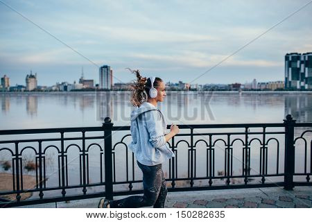 Young woman wearing headphones running in the city on river bank