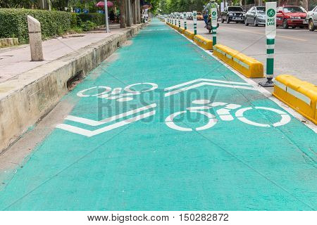 Bicycle lane with white bicycle sign .