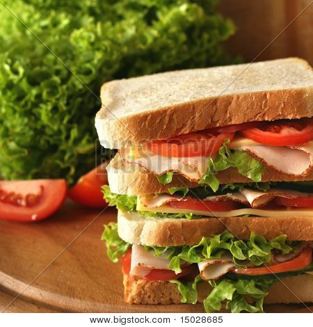 Huge sandwich with fresh ham, salad, gherkin and tomatoes. Shallow depth of field.