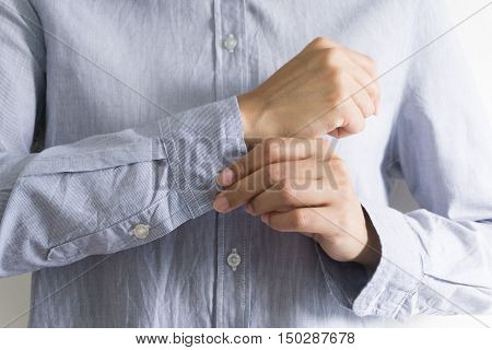 Woman dressing up and fastening buttons on shirt at home.