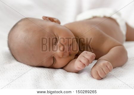 Three weeks old baby sleeping on white blanket cute infant newborn lying down close up shot eyes closed
