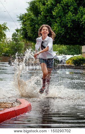 Enthusiastic girl runs through a puddle in a parking lot. She is wearing a long sleeve white shirt and clip on tie. She has on jean shorts and almost knee high socks. Water droplets are flying in the air as the puddle splashes around her.