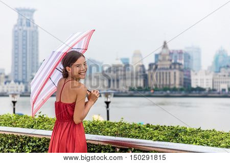 Beautiful young chinese woman enjoying walk on Pudong waterfront overlooking Huangpu district over the Bund, joyful under umbrella on a rainy summer day. Tourist travelling in Shanghai, China.