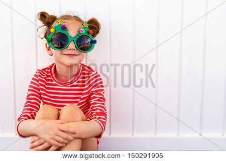Adorable little girl in a funny Christmas glasses over white background