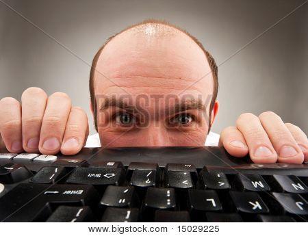 Timid Nerd Hiding Under Computer Keyboard