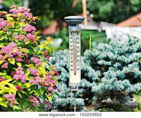 Modern outdoor thermometer in summer garden. Closeup.