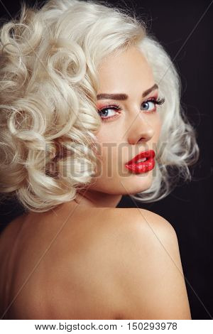 Vintage style portrait of young beautiful sexy blonde pin-up girl with curly hair and red lips, selective focus