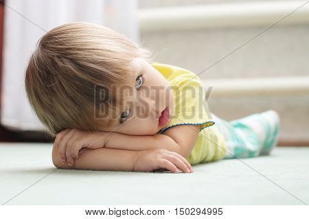 Little Caucasian girl lying on the floor on arms