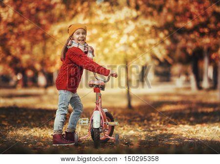 Cute little happy girl walking in autumn Park. Pretty child enjoys the beautiful autumn nature.